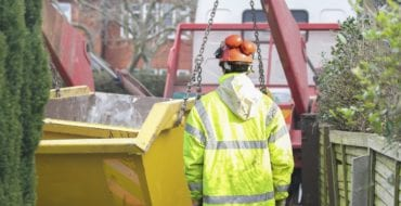 Builder landscaper supervising the delivery and unloading of a skip at a residential property