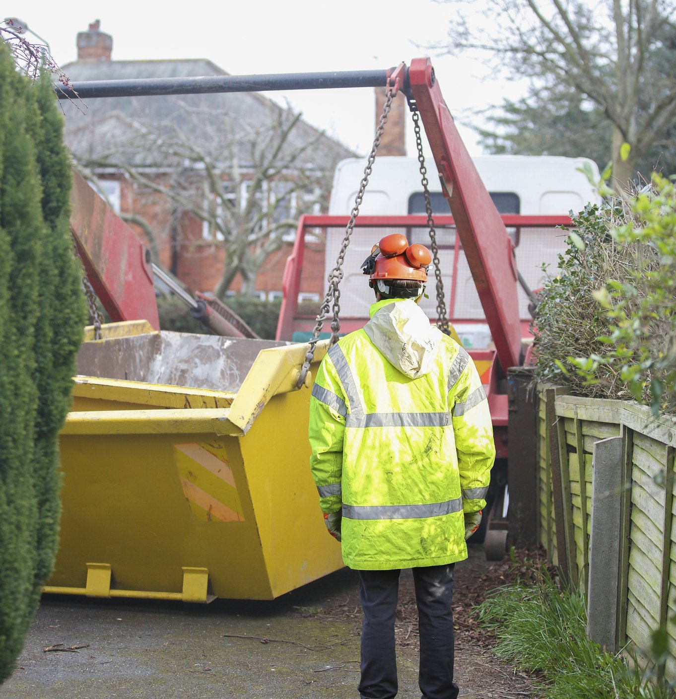 Builder supervising the delivery and unloading of a skip
